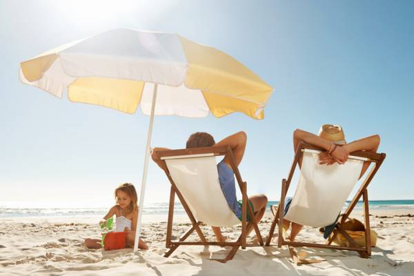 parents lounging on beach chairs with kid in the sand