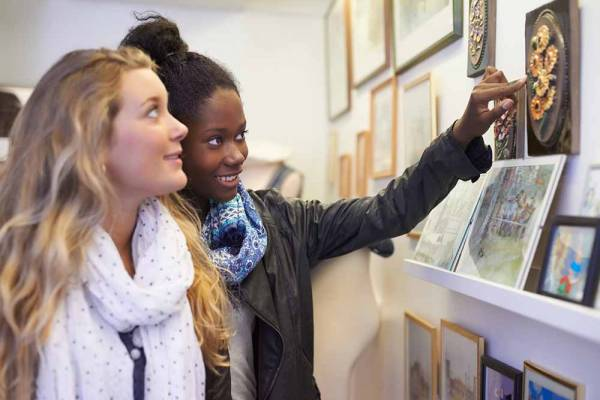 Girl friends looking at art in a gallery