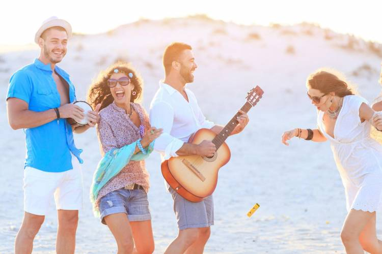 Friends playing guitar on the beach