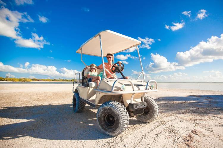 Dad and daughter on a golf cart on the beach