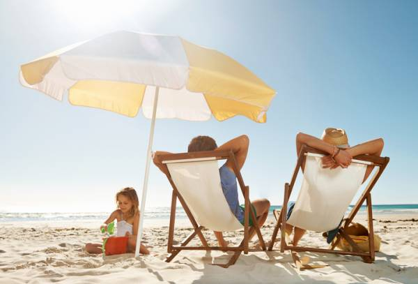 two adults lounging in yellow stripped beach chairs with matching umbrella and young daughter playing in sand