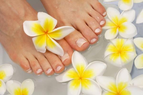 Freshly manicured feet in a flower bath
