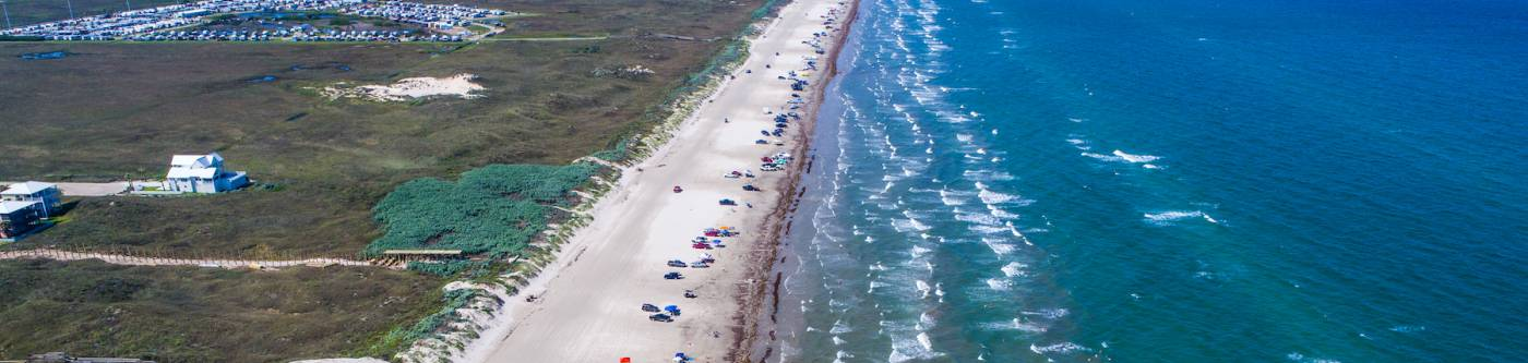 view of port aransas beach from above with cars parked on the sand