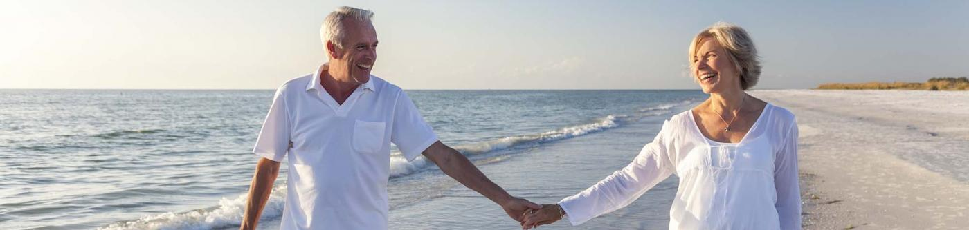 Snowbirds holding hands and walking on the beach in Texas